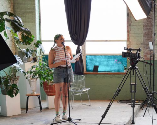 Poet reading from a text into a microphone in front of a large window white with sunlight