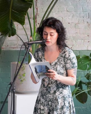 Female poet reading from a book into a microphone with a large plant behind