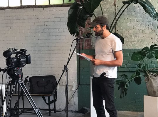 Poet reading from a text into a microphone